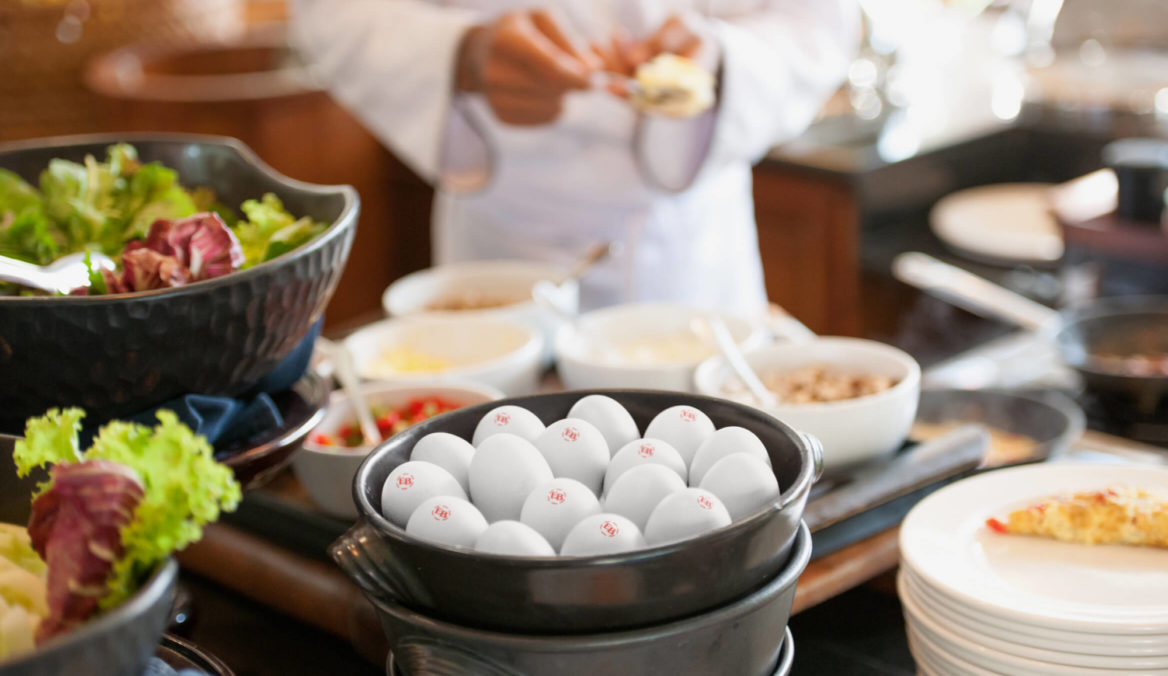 Photo of a bowl of eggs sitting within a professional kitchen.