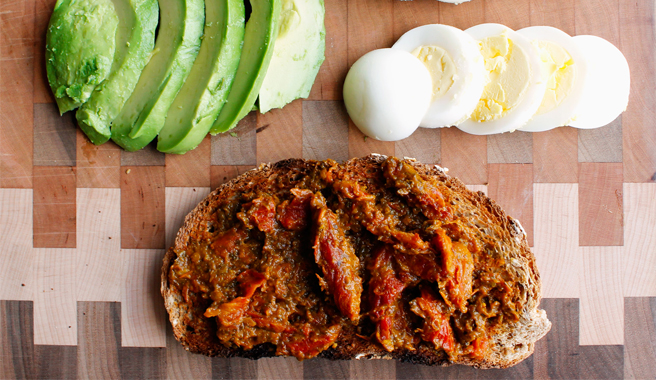 Toast topped with sundried tomato paste, avocado slices, and a sliced hard boiled egg